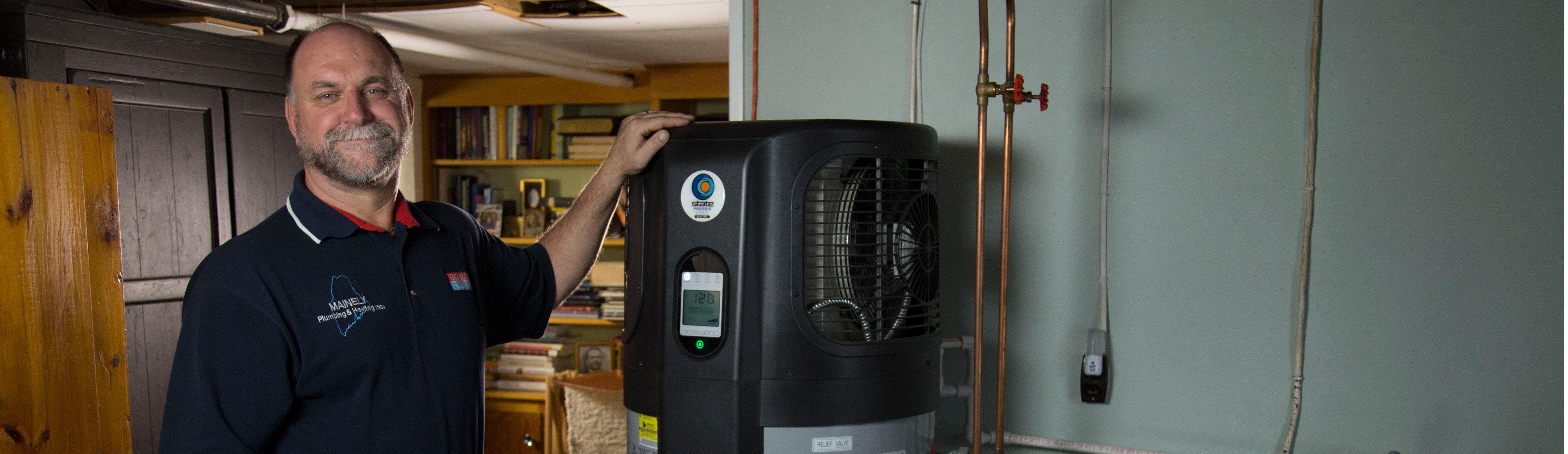 Man standing next to a heat pump water heater