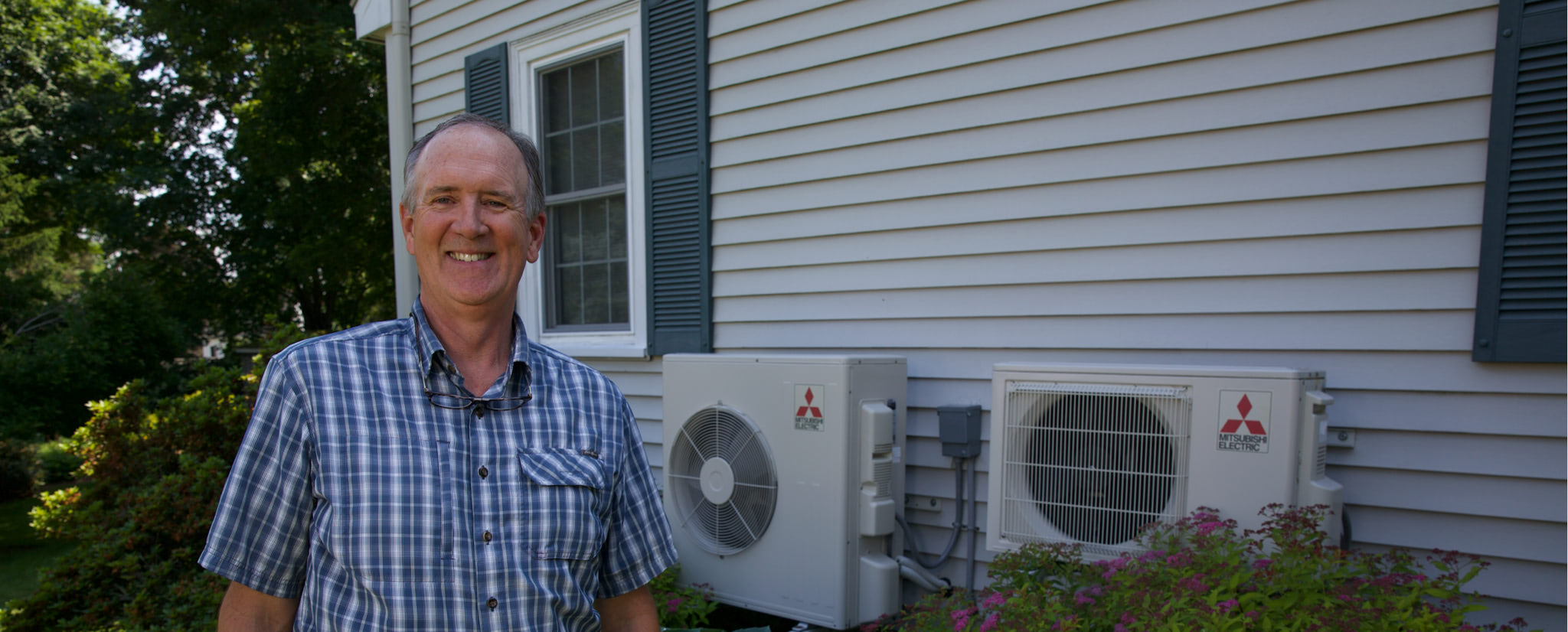 Man standing next to heat pumps attached to house.