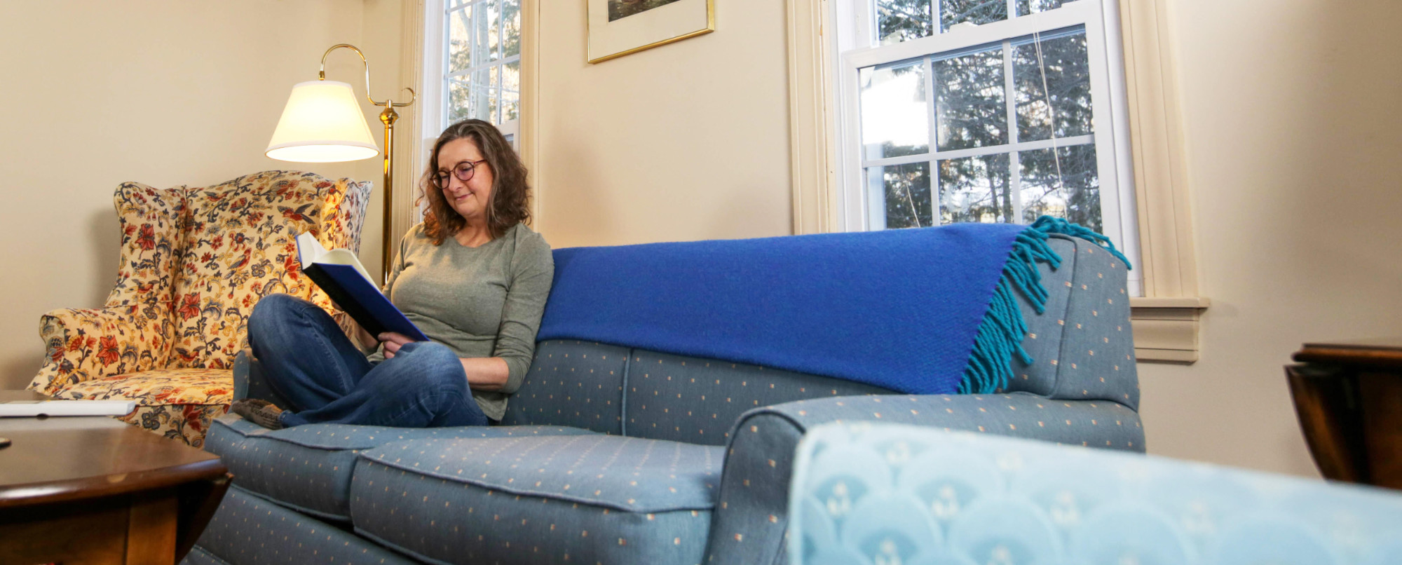 A woman reading while sitting on her living room couch